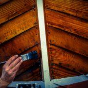 Hand streicht Holzboot mit Bootslack und Pinsel ein