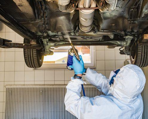 Unterbodenbeschichtung wird auf Auto angebracht